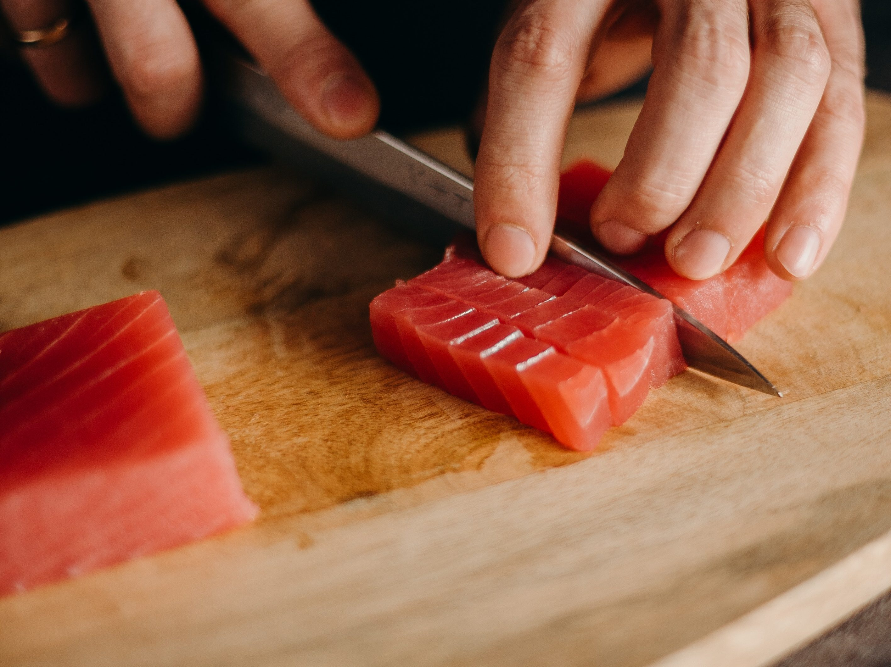 An image of a man slicing tuna to use it in a sushi recipe.